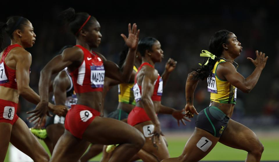 Jamaica's Shelly-Ann Fraser-Pryce, right, powers ahead to win gold in the women's 100-meter final during the athletics in the Olympic Stadium at the 2012 Summer Olympics, London, Saturday, Aug. 4, 2012. (AP Photo/Daniel Ochoa De Olza)