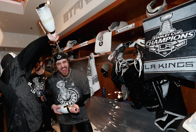 Los Angeles Kings center Anze Kopitar, of Slovenia, celebrates in the locker room after his team won the Stanley Cup in double overtime over the New Y...