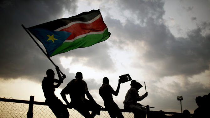 Southern Sudanese wave flags and cheer at the Republic of South Sudan's first national soccer match in the capital of Juba on Sunday, July 10, 2011. The game, played against Kenya, comes just one day after South Sudan declared its independence from the north following decades of costly civil war. (AP Photo/Pete Muller)
