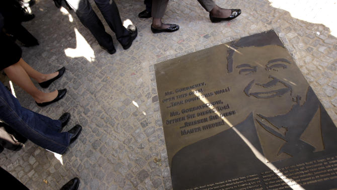 Guests stay around a plaque in honor of U.S. President Ronald Reagan right after it had been unveiled nearby the Brandenburg Gate during a remembrance ceremony in Berlin, Germany, Wednesday, Sept. 19, 2012. (AP Photo/Michael Sohn)