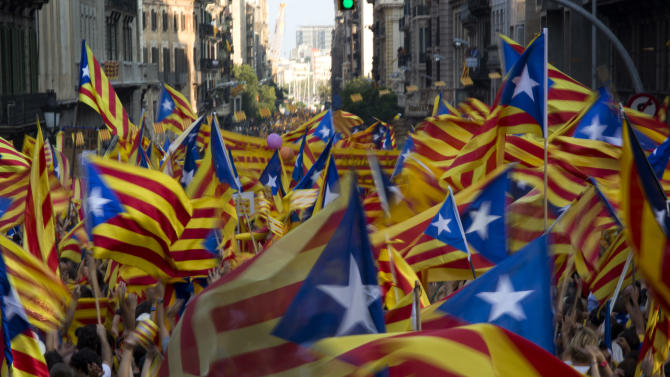 "FILE- In this  Sept. 11, 2012, file photo, demonstrators wave Catalan flags during a protest rally demanding independence for Catalonia, in north-eastern Spain, on the Catalan national day, in Barcelona, Spain. More than ever, FC Barcelona, known affectionately as Barca, lived up to its motto of being ""more than a club"" for this wealthy northeastern region where Spain's economic crisis is fueling separatist sentiment. Barca has been seen as a bastion of Catalan identity dating back to the three decades of dictatorship when Catalans could not openly speak, teach or publish in their native Catalan language. Barcelona writer Manuel Vazquez Montalban famously called the football team ""Catalonia's unarmed symbolic army.""(AP Photo/Emilio Morenatti, File)"