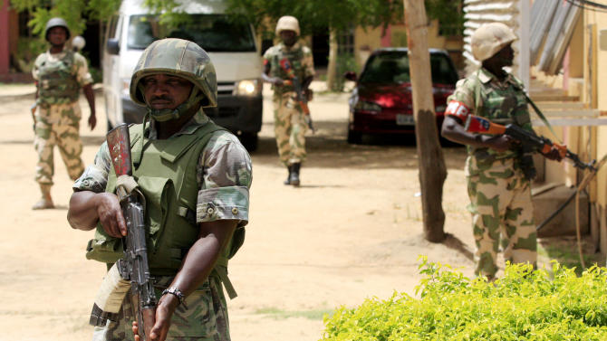 FILE - In this Thursday, June 6, 2013 file photo Nigerian soldiers stand guard at the offices of the state-run Nigerian Television Authority in Maiduguri, Nigeria. An environmental department official said Friday, Sept. 20, 2013 that workers combing bushes have recovered the bodies of at least 143 civilians killed by suspected Islamic militants in a Tuesday night attack on a major highway and Benisheik village, in Borno State, northeastern Nigeria. A soldier speaking on condition of anonymity Thursday said that extremists disguised in military fatigues attacked in 20 pickup trucks firing anti-aircraft guns that overwhelmed soldiers using automatic rifles and rocket-propelled grenades. (AP Photo/Jon Gambrell, File)