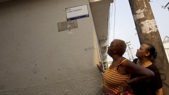 In this Dec. 28, 2012 photo, two residents look at a newly-installed street sign street in the Mare shantytown in Rio de Janeiro, Brazil.  The city's densest neighborhoods, its favelas, or shantytowns blanket entire hillsides, providing most of the city's affordable housing. Now, those communities are being charted after decades of informality, each route and alley outlined and their names researched. Being left off the map had meant whole communities were unable to receive mail at home. It had also blocked people from giving required information on job applications, getting a bank account or telling the police or fire department where to go in an emergency call. (AP Photo/Silvia Izquierdo)