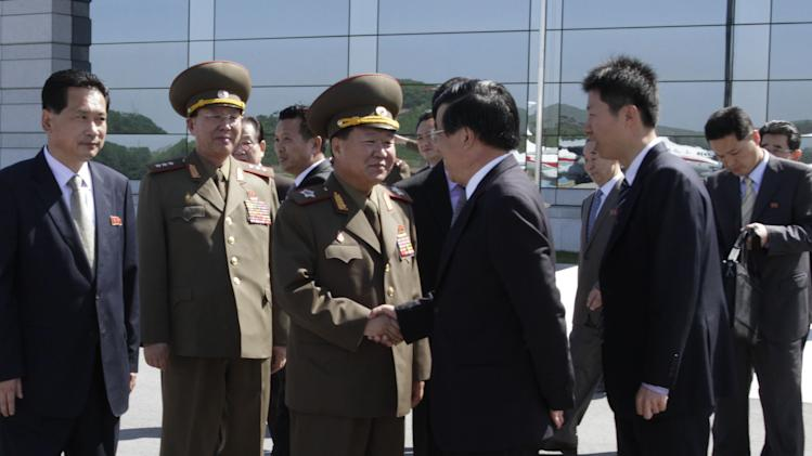 High-ranking North Korean party and military official Choe Ryong Hae, center left, shakes hands with Chinese Ambassador Liu Hongcai as Choe departs for China as a special envoy of North Korean leader Kim Jong Un, at Pyongyang airport, North Korea Wednesday, May 22, 2013. The trip by Choe, a vice marshal who is director of the General Political Bureau of the Korean People's Army, is the highest-profile visit by a North Korean official to neighboring China this year and takes place at as Beijing is under pressure to rein in Pyongyang's provocations. (AP Photo/ Kim Kwang Hyon)