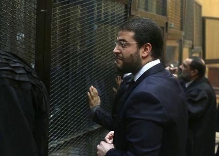 Osama Mohamed Morsi, son of Egypt's ousted president Mohamed Morsi, talks to Muslim Brotherhood members before the trial of the members including his father at a court on the outskirts of Cairo