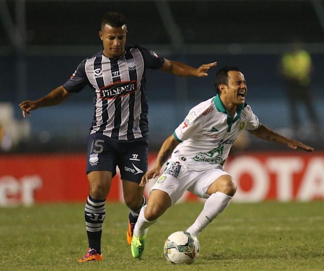 Luis Montes of Mexico's Leon, right, fights for the ball with Pedro Quinonez of Ecuador's Emelec, during a Copa Libertadores soccer match in Guayaquil, Ecuador, Tuesday, March 11, 2014