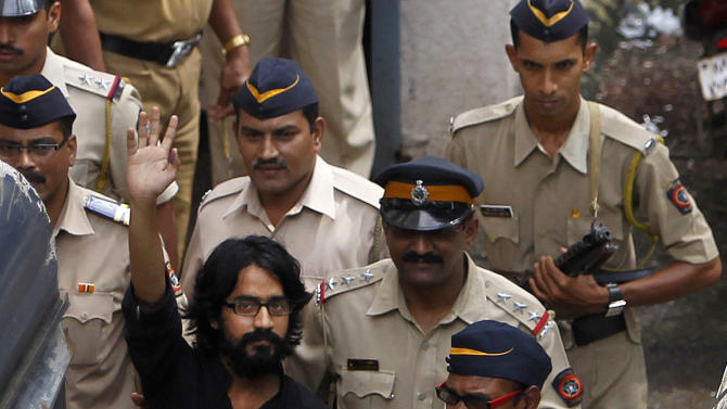 Indian policemen escort political cartoonist Aseem Trivedi to a court in Mumbai, India, Monday, Sept. 10, 2012. Trivedi whose drawings mock Indian government corruption has been jailed on a sedition charge in an arrest that was widely condemned Monday as evidence of political leaders' increasing intolerance of criticism. (AP Photo/Rafiq Maqbool)