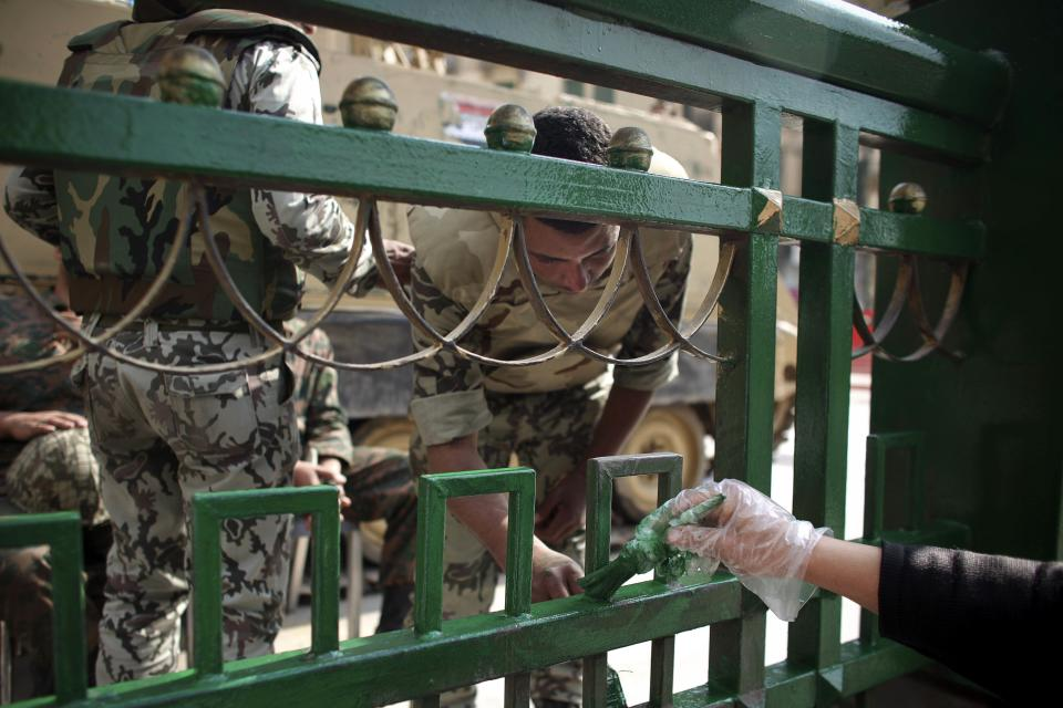 An Egyptian soldier helps a volunteer to paint a fence in Tahrir Square, Cairo, Egypt, Monday, Feb. 14, 2011. Egypt's military rulers dissolved parliament Sunday, suspending the constitution and promising elections in moves cautiously welcomed by pro-democracy protesters. (AP Photo/Tara Todras-Whitehill)