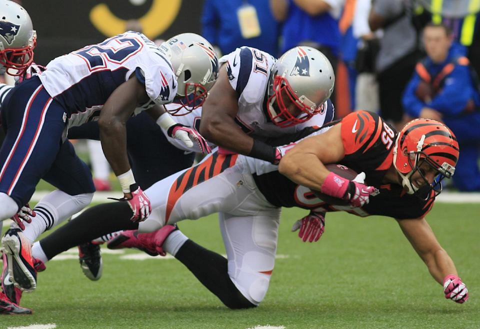 Cincinnati Bengals tight end Tyler Eifert (85) is tackled by New England Patriots outside linebacker Jerod Mayo (51) and free safety Devin McCourty (32) after a short gain in the first half of an NFL football game, Sunday, Oct. 6, 2013, in Cincinnati. (AP Photo/Tom Uhlman)