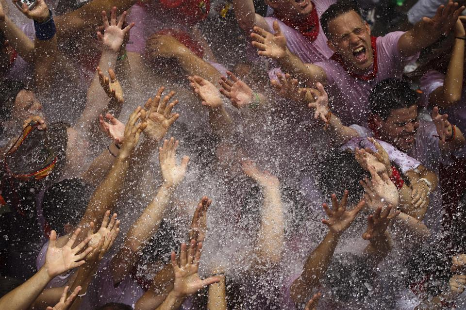 Revelers are sprayed with water after the 'Chupinazo', the official opening of the 2012 San Fermin fiestas, Friday, July 6, 2012 in Pamplona, Spain. Can we expect on Syrian Brig. Gen. Manaf Tlass had abandoned Assad's regime(AP Photo/Daniel Ochoa de Olza)