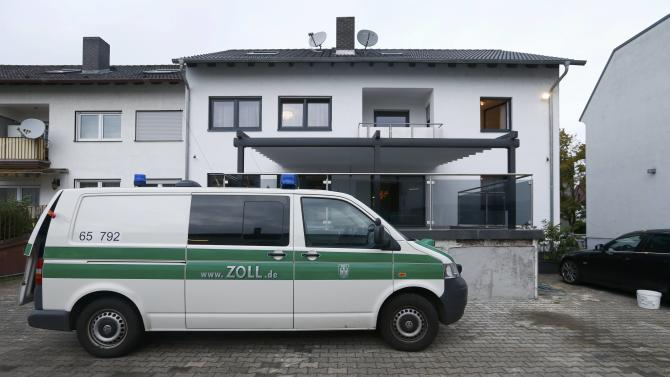 A customs vehicle stands in front of a residential house following an early morning raid in Ruesselsheim