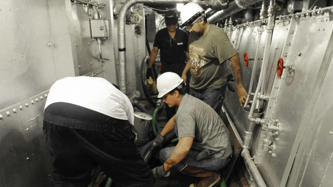 Men work to pump water from below the decks of the USS Texas Wednesday, June 13, 2012, in Houston. The 100-year-old battleship's hull sprung a leak five days ago and has been taking on as much as 1,000 gallons of seawater every minute as workers struggle to contain it. (AP Photo/Pat Sullivan)