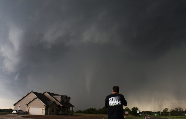 A storm chaser videographer and photographer records a tornado near a home in South Haven