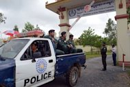 "Cambodian police sit in a pick-up truck as they leave the Extraordinary Chamber in the Courts of Cambodia (ECCC) in Phnom Penh. The former ""First Lady"" of Cambodia's murderous Khmer Rouge regime has been freed after the ECCC ruled she was unfit to stand trial"