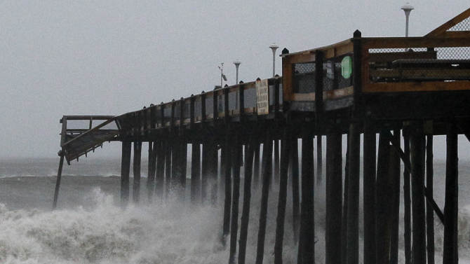 Waves crash against a partially damaged pier in Ocean City, Md., Sunday, Aug. 28, 2011, after Hurricane Irene churned along the Maryland coast overnight. Authorities in Ocean City said that there were no reports of major damage. (AP Photo/Patrick Semansky)