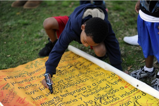MacCory writes message on banner in memory of teenager Martin as he joins others before a candlelight vigil in Sanford