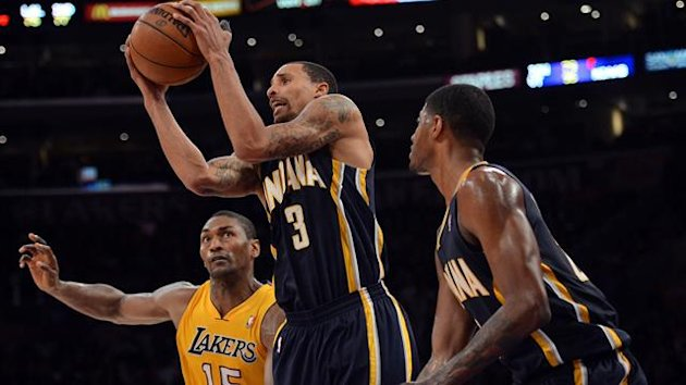 George Hill #3 of the Indiana Pacers grabs a rebound in front of teammate Paul George #24 and Metta World Peace #15 of the Los Angeles Lakers at Staples Center (AFP)