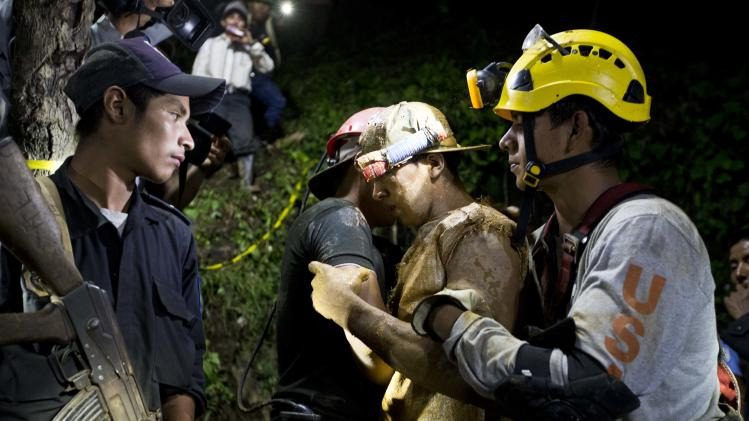A rescued miner, center, is accompanied by a rescue worker as he leaves on his own feet the entrance to the El Comal gold and silver mine in Bonanza, Nicaragua, Friday, Aug. 29, 2014.  The first 11 of 24 freelance gold miners trapped by a collapse in a mine have been rescued and crews were working early Saturday to free more, officials said. (AP Photo/Esteban Felix)
