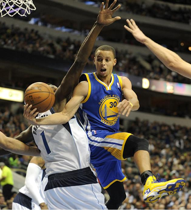 Golden State Warriors point guard Stephen Curry (30) passes around Dallas Mavericks center Samuel Dalembert (1) in the second half during an NBA basketball game on Wednesday, Nov. 27, 2013, in Dallas.