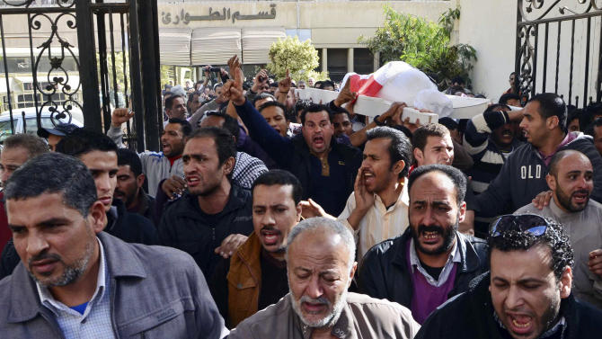 The body of Hossam Eldin Abdullah Abdelazim, 14, who activists say died when an armored police vehicle crushed him, is carried for burial from the international hospital in Mansoura, in the Nile Delta province of Dakahliya, Egypt, Saturday, March 2, 2013. Egypt's Interior Ministry says one protester has died and dozens have been wounded in violent anti-government clashes with police that erupted overnight and continued for several hours before dawn Saturday. (AP Photo/Sayed Baz)