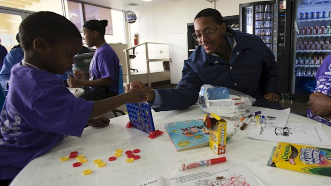 """Inmate Donald Parks plays game of Connect Four with son Dionte Jackson during special Father's Day visit part of """"Get On The Bus"""" program at California Men's Colony in San Luis Obispo"""