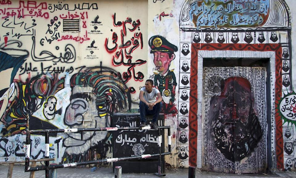 "An Egyptian man sits next to graffiti on a recently whitewashed wall in Tahrir Square, Cairo, Egypt, Friday, Sept. 28, 2012. The writing in Arabic, reads, ""Egypt is the grave of the Muslim Brotherhood,"" and ""when I leave your right I will be dead.""(AP Photo/Khalil Hamra)"