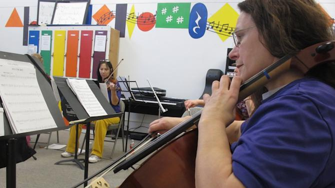 In this Nov. 17, 2012, photo, Dana Hilbish practices the cello with the Hiland Mountain Correctional Facility Orchestra in Eagle River, Alaska. Founding member, cellist Dana Hilbish, was convicted for the 1991 murder of her common law husband in Ketchikan. She received a 60-year sentence, with 25 suspended. This Saturday will will be her last performance. Hilbish has been granted parole early next year. (AP Photo/Mark Thiessen)