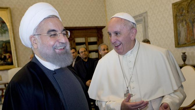 Pope Francis and Iranian President Hassan Rouhani, left, share a laugh during their private audience at the Vatican,Tuesday, Jan. 26, 2016. Iran's president has paid a call on Pope Francis at the Vatican during a European visit aimed at positioning Tehran as a potential top player in efforts to resolve Middle East conflicts, including Syria's civil war. (AP Photo/Andrew Medichini, Pool)
