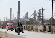 A cyclist rides along a dusty road where dozens of factories are processing rare earths on the outskirts of Baotou city in Inner Monglia, northwest China on April 21, 2011. China's largest rare earths producer said Tuesday it would suspend output at some plants for another month, extending a halt started in late October to try and stem falling prices