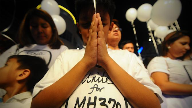 A young Malaysian boy prays, at an event for the missing Malaysia Airline, MH370, at a shopping mall, in Petaling Jaya, on the outskirts of Kuala Lumpur, Malaysia, Tuesday, March 18, 2014. A coalition of 26 countries, including Thailand, are looking for Malaysia Airlines Flight 370, which vanished March 8 with 239 people aboard on a night flight from Kuala Lumpur to Beijing. Search crews are scouring two giant arcs of territory amounting to the size of Australia — half of it in the remote seas of the southern Indian Ocean. (AP Photo/Joshua Paul)