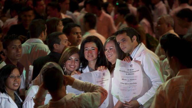 "FILE - In this July 18, 2012 file photo, just graduated doctors have their picture taken holding their diplomas after a graduation ceremony at the Karl Marx theater in Havana, Cuba. A Cuban doctor says the Caribbean nation is eliminating longstanding restrictions on health care professionals' overseas travel as part of a broader migration reform. The doctor says hospital directors met Saturday, Jan. 5, 2013 with Health Minister Roberto Morales and were told of the new policy, effective Jan. 14. For many years Cuban physicians have been limited in their ability to travel or had to undergo cumbersome bureaucratic procedures. But now they are supposed to be treated ""like any other citizen"" when it comes to traveling abroad. (AP Photo/Ramon Espinosa, File)"