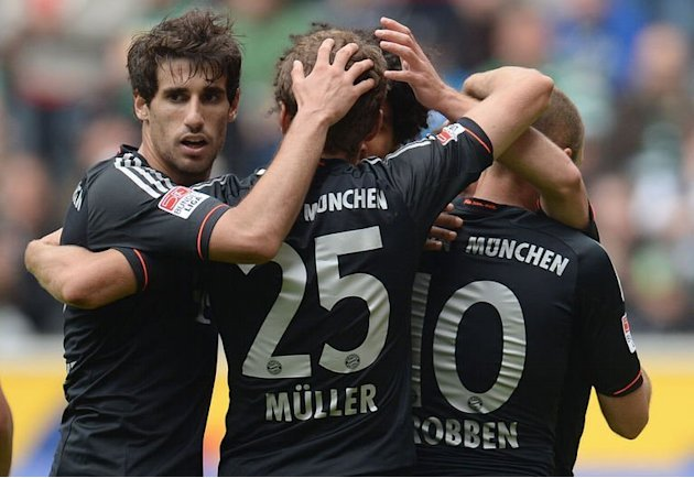 Bayern Munich's Arjen Robben, Javier Martinez and Thomas Mueller celebrate scoring at M'gladbach, on May 18, 2013