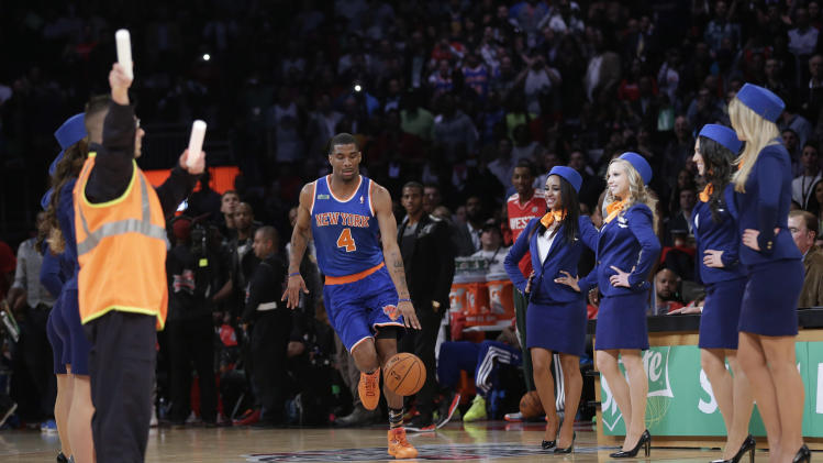 "James White of the New York Knicks is flanked by ""flight attendants"" during the dunk contest at NBA basketball All-Star Saturday Night, Feb. 16, 2013, in Houston. (AP Photo/Eric Gay)"