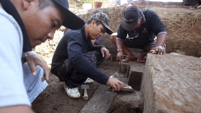 Balinese archaeologists work on the ancient temple structure in Denpasar, Bali, Indonesia on Friday, Oct. 26, 2012.  An archaeologist says a structure that is believed to be the remains of an ancient Hindu temple has been unearthed on Indonesia's resort island of Bali.  (AP Photo/Firdia Lisnawati)