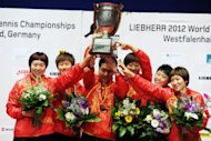 China's women team (L to R) Yan Guo, Ning Ding, headcoach Zhihao Shi, Shiwen Liu Yue Guo, Xiaoxia Li pose for a picture with the trophy during the flower ceremony on the podium, in Dortmund, western Germany. China completed the cleansweep of gold medals at the world team table tennis championship on Sunday as their women's team beat defending champions Singapore 3-0 in Sunday's final