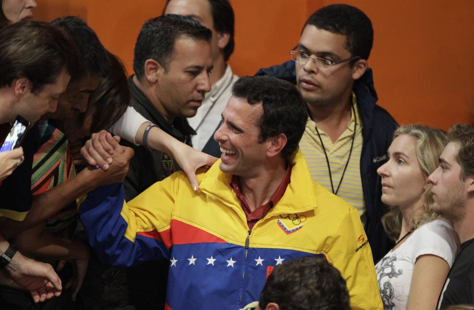 Opposition presidential candidate Henrique Capriles, center, is greeted by supporters after he conceded defeat in the presidential elections at his campaign headquarters in Caracas, Venezuela, Sunday, Oct. 7, 2012.  Venezuela's electoral council said late Sunday President Hugo Chavez has won re-election, defeating challenger Henrique Capriles. (AP Photo/Ariana Cubillos)
