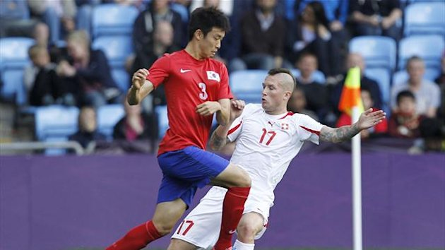 South Korea's Yun Suk-young (L) fights for the ball with Switzerland's Michel Morganella during their men's Group B football match in the London 2012 Olympic Games (Reuters)