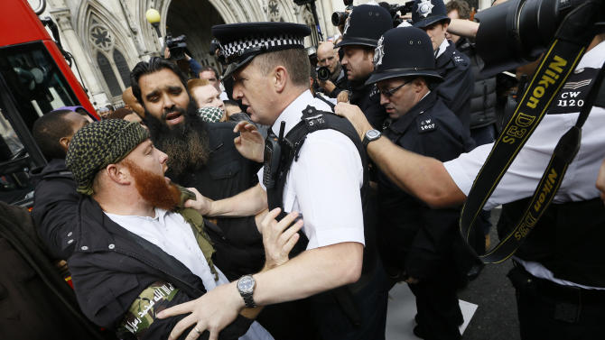Demonstrators clash with police officers outside The Royal Courts of Justice in London Friday, Oct. 5, 2012. Radical Islamic cleric Abu Hamza and four other terror suspects are expected to find out today if they have won their latest legal move to avoid extradition from the UK to America for trial on terrorism charges. (AP Photo/Kirsty Wigglesworth)