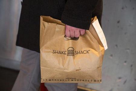 A customer holds a bag full of food inside of a Shake Shack store in New York