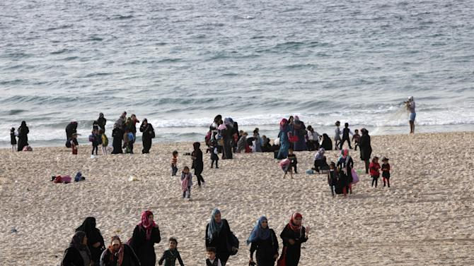 FILE - In this Thursday, Oct. 31, 2013 file photo, Palestinian families enjoy the beach of the Mediterranean Sea in Gaza City. Palestinians continue to have a higher rate of natural growth than Jews, and leading Israeli demographers have said the current slight Jewish majority in the Holy Land will disappear in a few years. Israelis in favor of a peace deal that cedes most of the war-won land to a Palestinian state usually point to the ``demographic time bomb'' as a prime motivator. (AP Photo/Adel Hana)