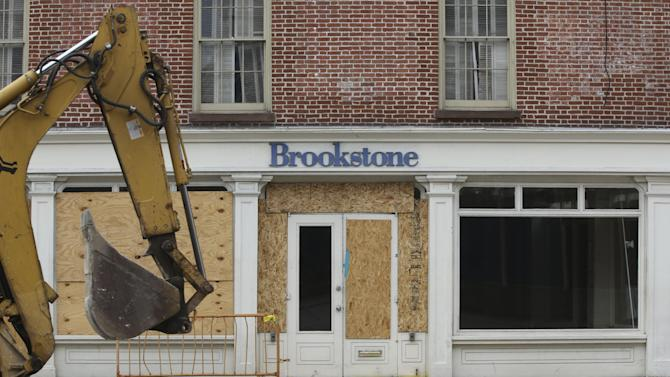 In this Thursday, Feb. 7, 2013 photo, a backhoe is driven past the shuttered Brookstone store on Fulton St. in New York. Nearly four months after Superstorm Sandy hit, the historic cobblestone streets near the water's edge in lower Manhattan are eerily deserted, and among local business owners, there is a pervasive sense that their plight has been ignored by the rest of Manhattan. (AP Photo/Mary Altaffer)