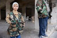 A Syrian boy wearing a military vest stands next to a rebel at a checkpoint manned by the Free Syrian Army (FSA) in the Bustan al-Basha district in the northern city of Aleppo