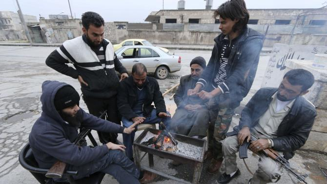 Rebel fighters and civilians warm themselves around a fire in Tariq al-Bab neighbourhood of Aleppo