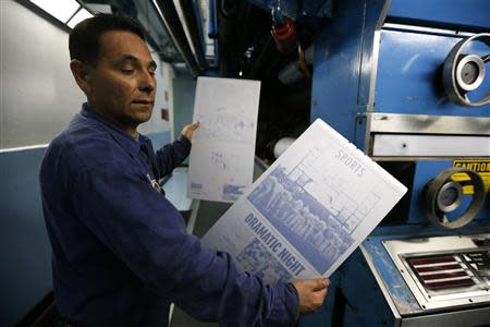 Printer Jose Lomeli holds newspaper printing plates for the first copies of the inaugural Los Angeles Register newspaper in Santa Ana