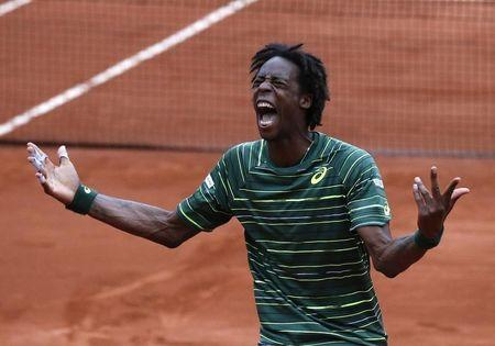 Gael Monfils of France celebrates after beating Pablo Cuevas of Uruguay during their men's singles match at the French Open tennis tournament at the Roland Garros stadium in Paris