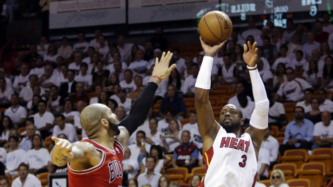 Miami Heat guard Dwyane Wade (3) shoots against Chicago Bulls forward Carlos Boozer (5) during the first half of Game 2 of their NBA basketball playoff series in the Eastern Conference semifinals, Wednesday, May 8, 2013, in Miami. (AP Photo/Lynne Sladky)