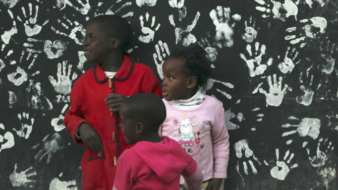 Girls stand in front a mural with hand prints on a wall at the Alexandra township in Johannesburg, South Africa, Tuesday, July 17, 2012,  on a mural designed to honor former President Nelson Mandela's 94th birthday which is celebrated Wednesday, July 18. (AP Photo/Themba Hadebe)