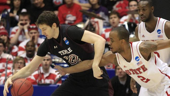 CORRECTS BYLINE - North Carolina State guard Lorenzo Brown (2) reaches in on Temple forward Jake O'Brien (22) during the first half of a second-round game at the NCAA college basketball tournament, Friday, March 22, 2013, in Dayton, Ohio. (AP Photo/Skip Peterson)