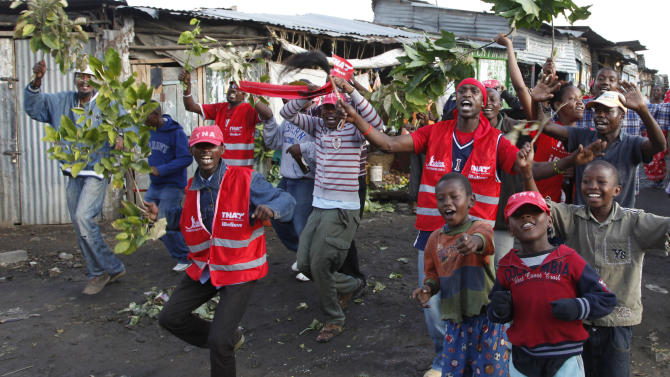 Supporters of Kenyan presidential candidate Uhuru Kenyatta celebrate in Nairobi, Kenya Saturday, March 9, 2013. Kenya's election commission posted complete results early Saturday showing that Deputy Prime Minister Uhuru Kenyatta prevailed in the country's presidential elections by the slimmest of margins, winning 50.03 percent of the vote.(AP Photo/Sayyid Azim)