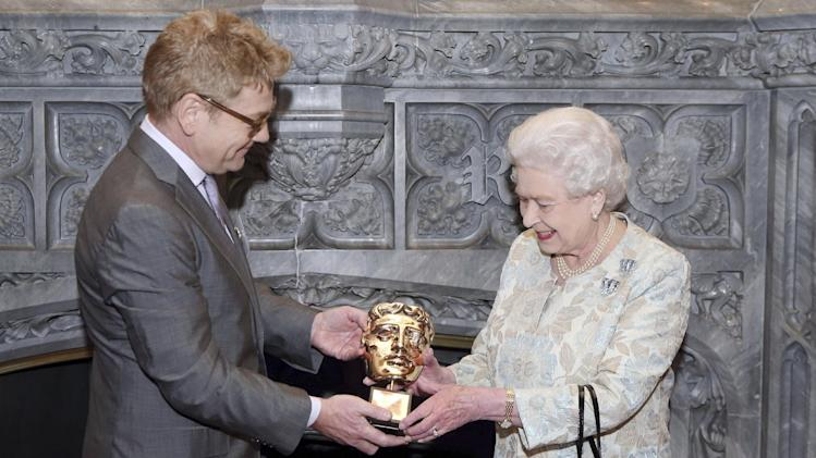 "Queen Elizabeth II receives an honorary British Academy award (Bafta) Thursday April 4 2013,  at Windsor Castle, west of London, from  actor and director Kenneth Branagh, in recognition of her lifetime's support of British film and television - and for being the most ""memorable Bond girl yet"", in her London Olympics opening role. (AP Photo/Steve Parsons, pool)"